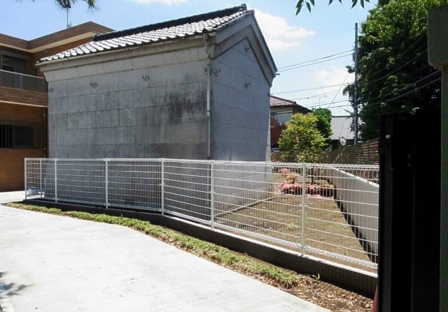 真新しいRC住宅とフェンスの隙間で居心地が悪そうな「蔵」